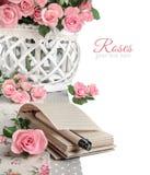 Leeres Notizbuch unter den schönen rosa Rosen, lokalisiert auf Weiß Ha Lizenzfreie Stockfotografie