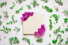 Leeres Notizbuch verzierte purpurrote Blumen auf einem wei?en Hintergrund, Draufsicht Notizblock verziert mit gr?nen Bl?ttern und stock abbildung