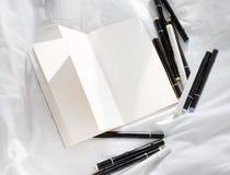 Leeres offenes Tagebuch auf einem weißen Bett mit Stapel von Stiften lizenzfreies stockbild
