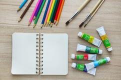 Leeres Papier, Acrylfarbe und bunte Bleistifte auf dem hölzernen tabl Lizenzfreies Stockbild
