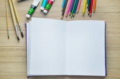 Leeres Papier, Acrylfarbe und bunte Bleistifte auf dem hölzernen tabl Stockfotos