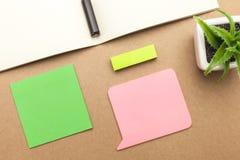 Leeres Papier, Buch, Stift und Anlage auf braunem Hintergrund Lizenzfreies Stockfoto