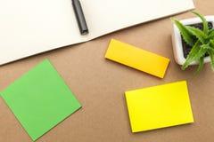 Leeres Papier, Buch, Stift und Anlage auf braunem Hintergrund Lizenzfreies Stockbild