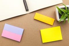 Leeres Papier, Buch, Stift und Anlage auf braunem Hintergrund Lizenzfreie Stockfotografie