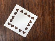 Leeres Papier des weißen Quadrats, das in der Herzform auf dunkelbrauner hölzerner Tabelle gelocht wurde stockfotos
