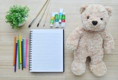 Leeres Papier, Farbfarbe und Bärnpuppe auf die hölzerne Tischplatte V Stockfotografie