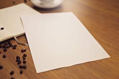 Leeres Papier mit einem Notizbuch mit einem Tasse Kaffee lizenzfreie stockfotografie