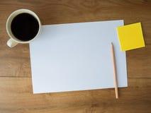 Leeres Papier mit Kaffeetasse und Anmerkung und Bleistift auf hölzernem backgr Stockfotos