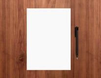 Leeres Papier mit Stift auf Schreibtisch Stockfotografie