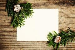 Leeres Papier mit Tannenzweig auf hölzernem Abstraktes Hintergrundmuster der weißen Sterne auf dunkelroter Auslegung Stockfotos