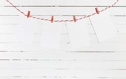 Leeres Papier oder Foto gestaltet das Hängen an der roten gestreiften Wäscheleine Auf hölzernem Hintergrund Schablone für Ihren T lizenzfreies stockfoto