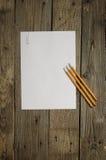 Leeres Papier und Bleistifte auf dunklem hölzernem Hintergrund Stockbilder