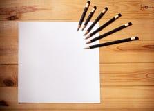 Leeres Papier und Bleistifte auf hölzernem Hintergrund Stockbilder