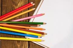 leeres Papier und bunte Bleistifte auf altem Holztisch Lizenzfreie Stockbilder