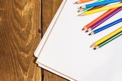 leeres Papier und bunte Bleistifte auf alter hölzerner Plattform Lizenzfreie Stockbilder