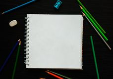 Leeres Papier und bunte Bleistifte auf dem dunklen Holztisch Stockfotos