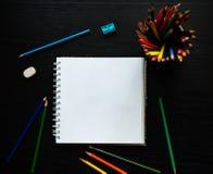 Leeres Papier und bunte Bleistifte auf dem dunklen Holztisch Lizenzfreies Stockbild