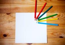Leeres Papier und bunte Bleistifte auf dem hölzernen Hintergrund Stockbild