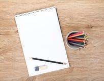 Leeres Papier und bunte Bleistifte auf dem Holztisch Stockfotografie