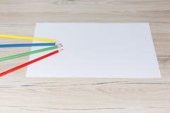 Leeres Papier und bunte Bleistifte auf dem Holztisch Ansicht von oben Stockbilder