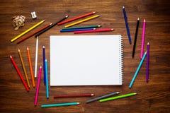 Leeres Papier und bunte Bleistifte auf dem Holztisch Beschneidungspfad eingeschlossen Lizenzfreie Stockfotos