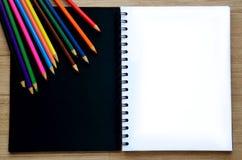 Leeres Papier und bunte Bleistifte auf der hölzernen Tischplatteansicht Stockbild