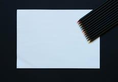 Leeres Papier und bunte Bleistifte auf schwarzem Hintergrund Stockbild