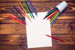 Leeres Papier und farbige Bleistifte auf einem Holztisch Lizenzfreie Stockfotografie