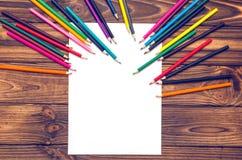 Leeres Papier und farbige Bleistifte auf einem Holztisch Stockfoto