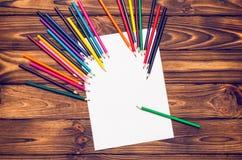 Leeres Papier und farbige Bleistifte auf einem Holztisch Lizenzfreies Stockbild