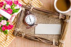 Leeres PapierTag und Uhr mit fram und Blume der Weinlese auf hölzernem Lizenzfreie Stockbilder