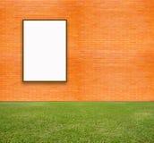 Leeres Plakat mit Backsteinmauer und grünem Rasen Stockfotografie