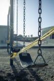 Leeres Plastikschwingen auf Spielplatz mit Vorsichtband, selektiver Fokus Stockbild