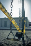 Leeres Plastikschwingen auf Spielplatz mit Vorsichtband, selektiver Fokus Lizenzfreie Stockfotografie