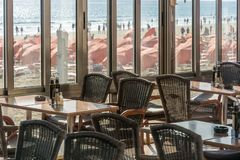 Empty restaurant overlooking a full beach stock images