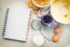 Leeres Rezeptnotizbuch mit Käsekuchenbestandteilen bereitete sich über einen weißen hölzernen Hintergrund vor Stockbild