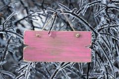Leeres rosa Holzschild mit Eis umfasste Baumaste Stockfotografie