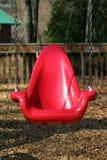 Leeres rotes Eimerschwingen an einem Parkspielplatz Stockfotos