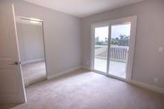 Leeres Schlafzimmer mit großer Glasschiebetür zur Plattform des Hinterhofes in Süd-Kalifornien-Haus lizenzfreie stockfotografie