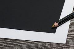 Leeres schwarzes Papier und bunter Bleistift auf dem Holztisch Stockfotografie
