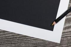 Leeres schwarzes Papier und bunter Bleistift auf dem Holztisch Lizenzfreies Stockbild