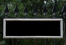 Leeres Schwarzweiss-Zeichen angebracht an den schwarzen Geländern Stockfotografie
