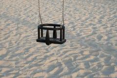 Leeres Schwingen Seat für Kinder mit weißem Sand im Hintergrund stockfoto