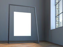 Leeres Segeltuch, das am modernen Stand im grauen Innenraum hängt Lizenzfreie Stockbilder