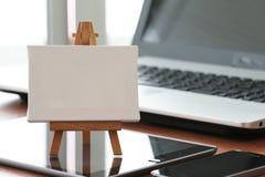 Leeres Segeltuch und hölzernes Gestell auf Laptop-Computer Stockfotografie