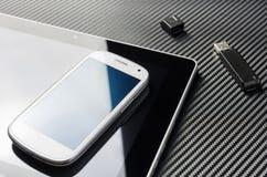 Leeres Smartphone mit der blauen Reflexion, die auf Geschäfts-Tablet nahe bei einem offenen USB-Speicher-Blitz-Antrieb über einem Lizenzfreies Stockbild