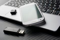 Leeres Smartphone mit der grünen Reflexion, die auf Geschäfts-Notizbuch-Tastatur nahe bei einem USB-Speicher, alle über einer Koh Lizenzfreie Stockfotografie