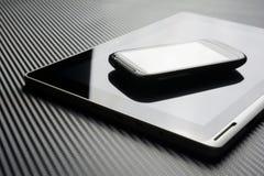 Leeres Smartphone mit der Reflexion, die auf Geschäfts-Tablet mit Reflexion auf Kohlenstoff-Hintergrund liegt Stockbilder
