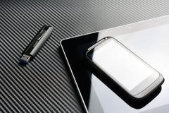 Leeres Smartphone mit der Reflexion, die auf Geschäfts-Tablet nahe bei einem USB-Speicher-Blitz-Antrieb über einem Kohlenstoff-Hi Stockfoto