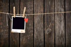 Leeres sofortiges Foto und kleines rotes Papierherz Lizenzfreies Stockbild